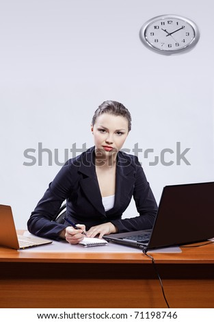 office portrait of beautiful young serious business woman sitting at her workplace with two laptops on gray