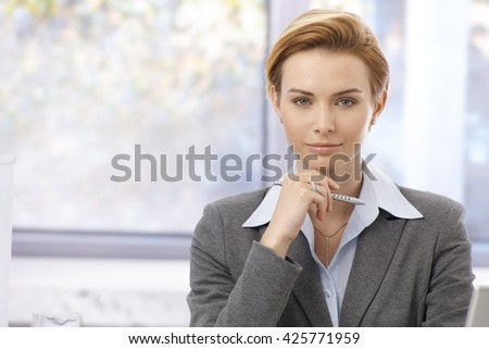 Office portrait of young attractive businesswoman in shirt and jacket, looking at camera. - stock photo