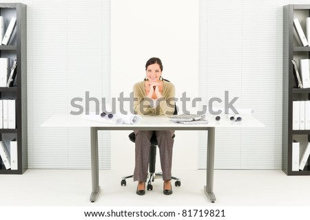 Office professional architect female with blueprints sitting behind table - stock photo