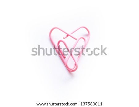 Office romance. Two pink paperclips forming a heart in a symbol of love and romance.