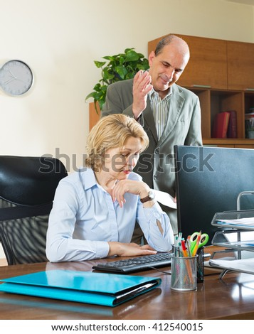 Office scene with angry chief and careless aged secretary - stock photo