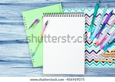 Office set with notebooks, colored pencils and pens on blue wooden background
