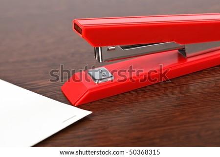 office stapler on wooden table - stock photo
