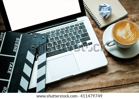 office stuff with Movie clapper laptop and coffee cup pen notepad on the wood table top view shot.dark effect - stock photo