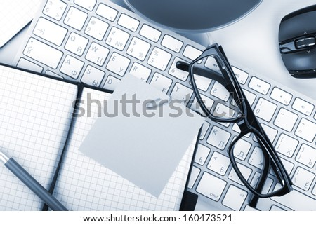 Office supplies and computer keyboard. Closeup blue toned - stock photo