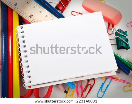 office supplies and notebook with blank sheet