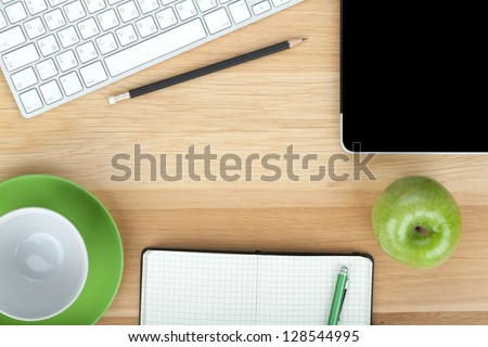 Office supplies, devices, coffee cup and apple on wooden table - stock photo