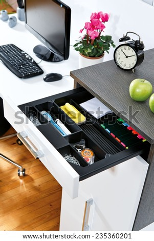 Office supplies in open desk drawer  - stock photo