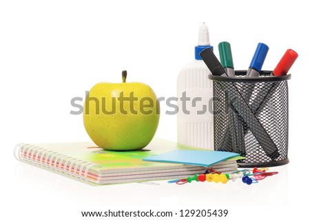 Office supplies - markers, exercise book and green apple isolated on white background - stock photo