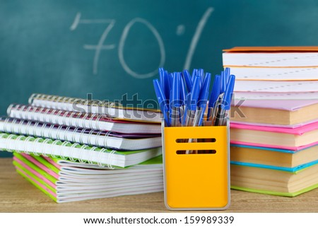 Office supplies on table on school board background