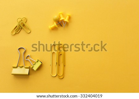 Office supply - binder clip, push pins and paper clip on yellow background - stock photo