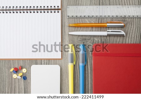 Office supply collection - highlighter, thumbtacks, ball pens, notebooks and ruler - on brown wooden table. - stock photo