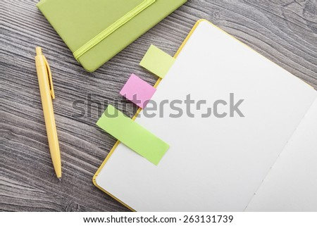 Office supply collection - notebooks, yellow ballpoint pen, colored flags - on brown wooden table. - stock photo