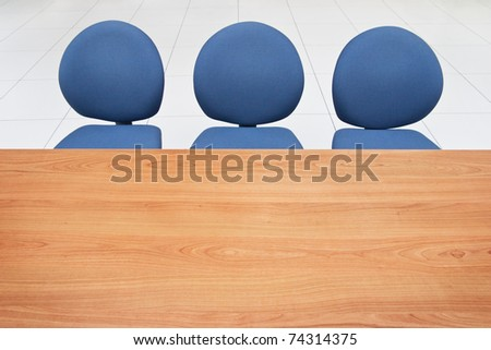 Office table and three chairs in a waiting room. - stock photo
