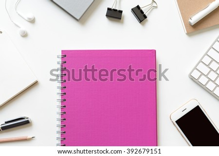 Office table desk with colorful book, notepaper, smart phone, fountain pen, clips, earphones, top view and copy space for text - stock photo