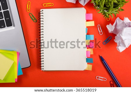 Office table desk with set of colorful supplies, white blank note pad, cup, pen, pc, crumpled paper, flower on red background. Top view and copy space for text. - stock photo