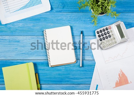 Office table desk with set of colorful supplies, white blank note pad, cup, pen, pc, crumpled paper, flower on blue wooden background. Top view and copy space for text. View from above - stock photo