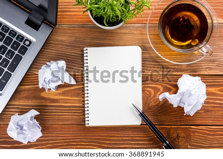 Office table desk with supplies, white blank note pad, cup, pen, pc, crumpled paper, flower on wooden background. Top view - stock photo