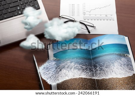 Office table in clouds with the sea on the notebook. Vacation concept - stock photo