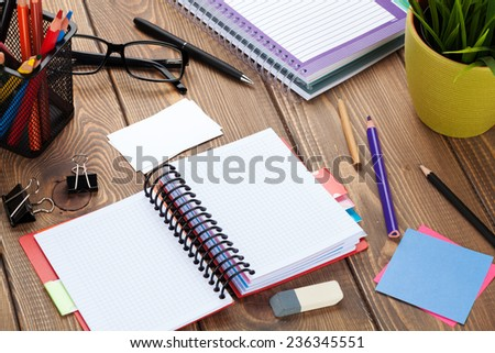 Office table with blank notepad and supplies. View from above with copy space - stock photo