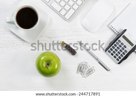 Office table with computer, notepad, thumb drive, mouse, silver pen, calculator, green apple, paper clips and black coffee. Top view angle with copy space.