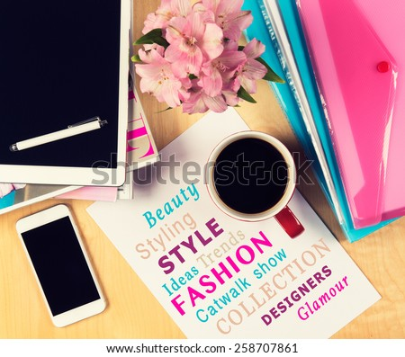 Office table with fashion magazines, digital tablet, smartphone and cup of coffee. View from above with copy space - stock photo