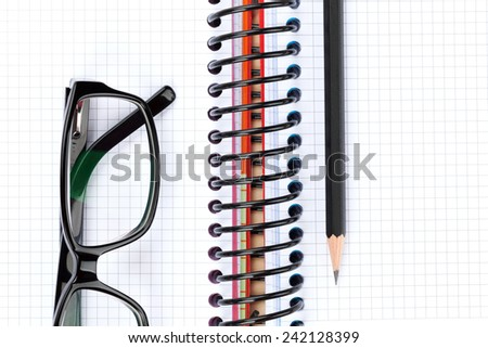 Office table with glasses, blank notepad and pencil. View from above - stock photo