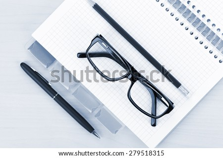 Office table with glasses, blank notepad and pencil. View from above