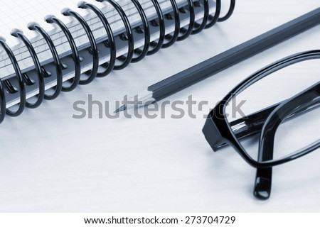 Office table with glasses, notepad and supplies. Blue toned image - stock photo
