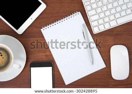 Office table with notebook, computer keyboard and mouse, tablet pc and smartphone