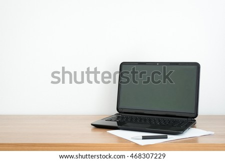 Office table with notepad and laptop