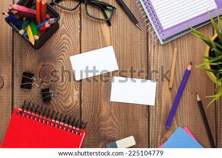 Office table with notepad, colorful pencils, supplies and business cards. View from above with copy space - stock photo