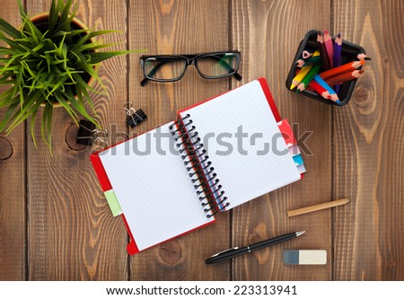 Office table with notepad, colorful pencils, supplies and flower. View from above with copy space - stock photo