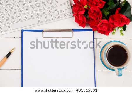 Office table with openbook,camera,pen,rose,keyboard and coffee cup.View from above with copy space.