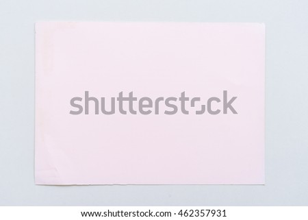 Office table with pink paper sheet, top view