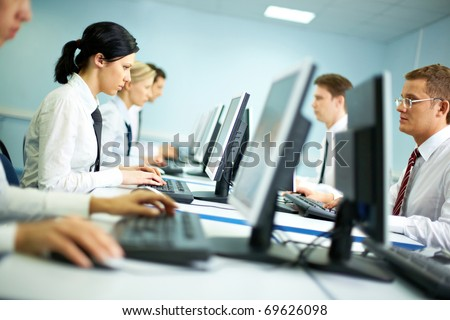 Office with white collar workers working on computers - stock photo
