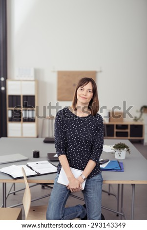 Office Woman Leaning her Back Against the Table at the Boardroom While Holding Notes and Smiling at the Camera. - stock photo