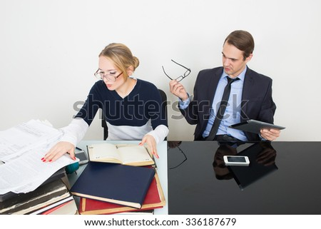 office. woman looking for information in books. The man speaks on the phone - stock photo