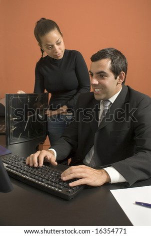 Office woman shows a businessman a giant clock while he types on his computer. Vertically framed photo.