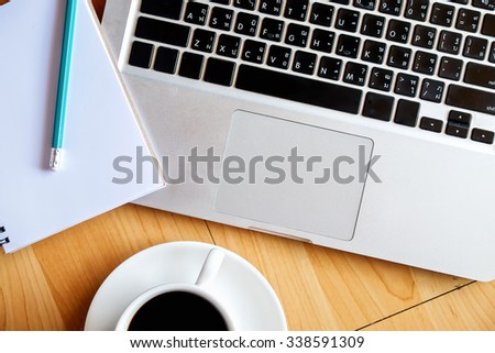 Office wood table with laptop notepad pencil and coffee cup . Top view