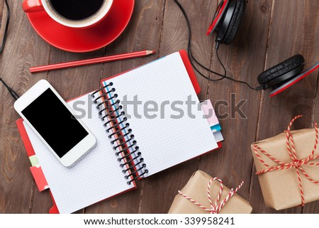 Office wooden desk with notepad, smartphone and gift boxes. Top view with copy space - stock photo