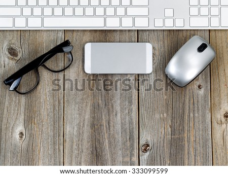 Office wooden desktop, boards running vertically, with computer keyboard, mouse and reading glasses. Top view in horizontal format.  - stock photo