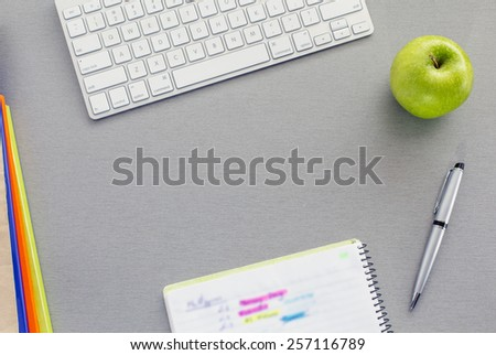 Office work space on grey desk with green apple. From above view on grey wooden desk with well organized office supplies and green apple. Notepad with hand notes marked with bright colors - stock photo