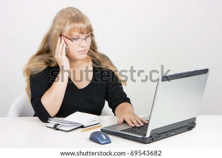 office worker. Blonde girl with laptop talking on a cell phone.