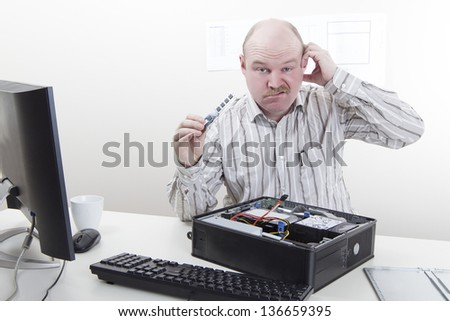 Office worker / businessman with computer / IT problems with a memory component in his hand. - stock photo