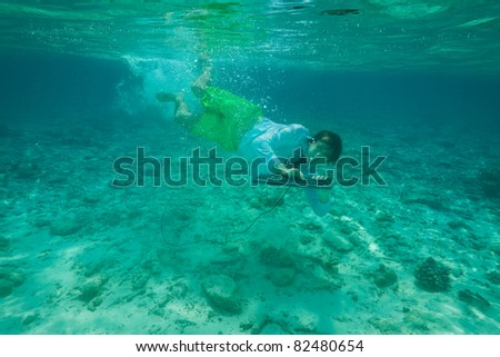 Office worker continue working even being underwater (wearing formal clothes and typing on keyboard) - stock photo