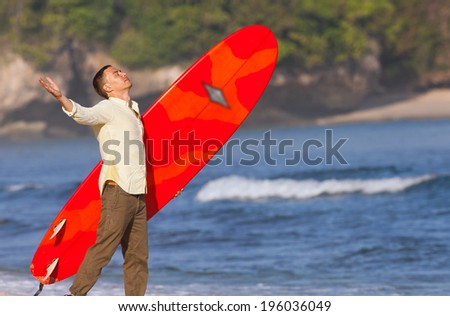 office worker enjoying their recreational activities near the sea with surfboard - stock photo