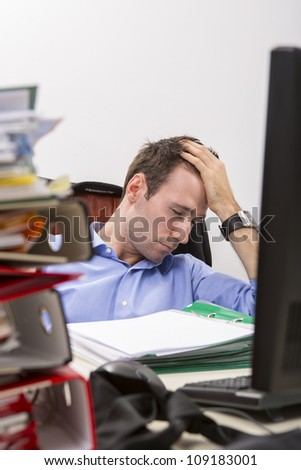 Office worker falls asleep by exhaustion at a desk full of massive stack of file folders.