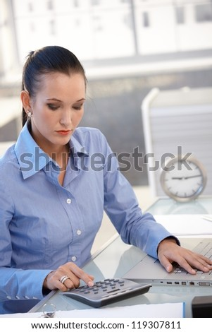 Office worker girl using calculator, busy with financial task at desk. - stock photo