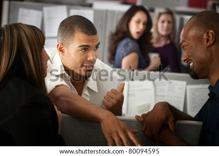 Office worker gossips about other lady in his cubicle - stock photo